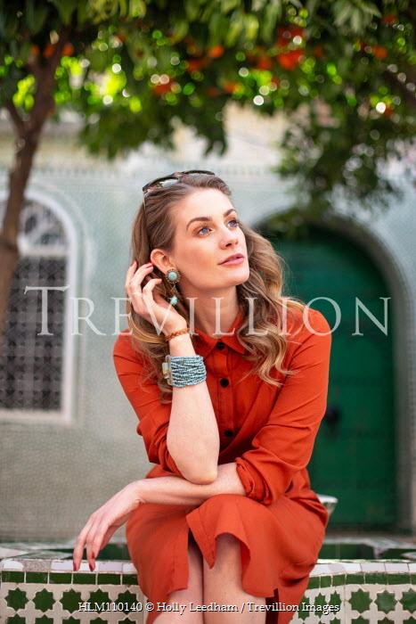 Holly Leedham WOMAN SITTING IN SUMMERY COURTYARD Women