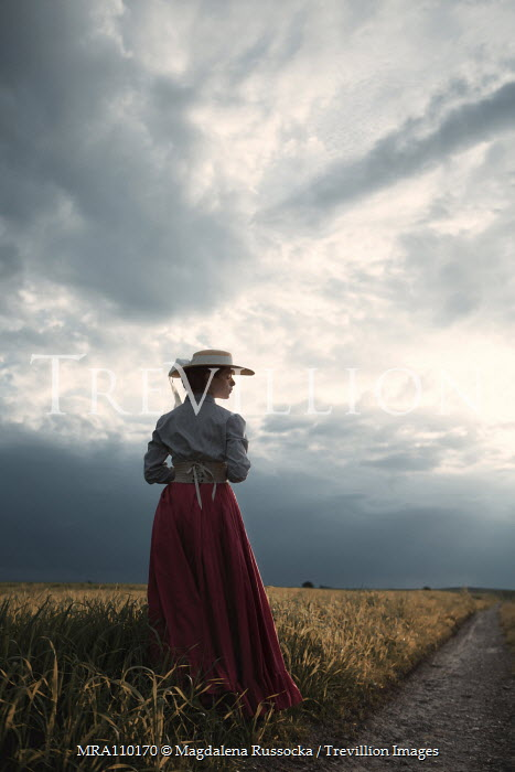 Magdalena Russocka historical woman standing in field with stormy sky
