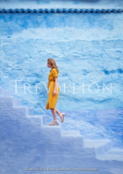 Holly Leedham WOMAN IN YELLOW DRESS CLIMBING STONE STEPS Women