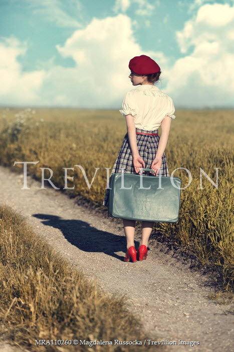 Magdalena Russocka retro woman with suitcase standing on country path