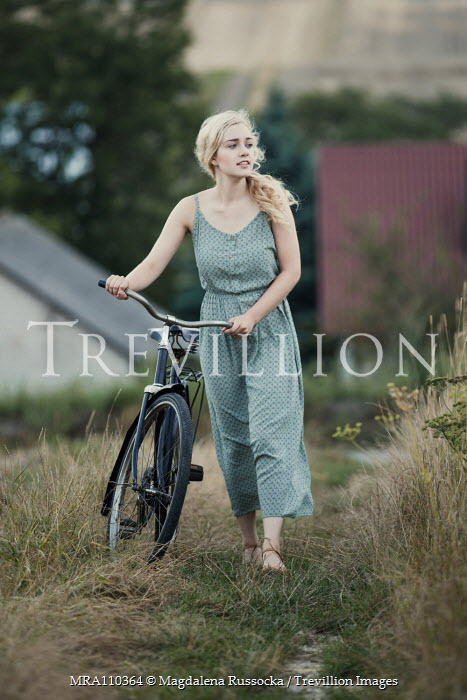 Magdalena Russocka young blonde woman with bike on country path