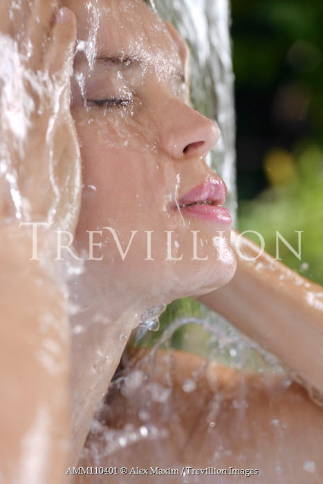Alex Maxim Young woman face showering under fresh pouring water outdoors