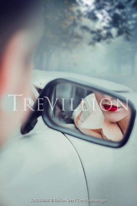 Ildiko Neer Red lips of woman reflected in car mirror
