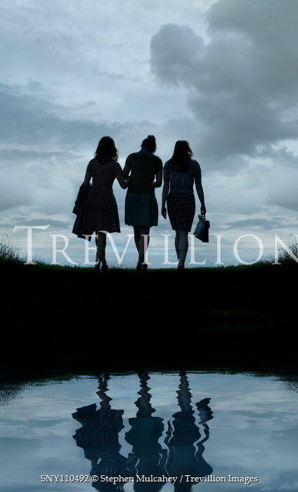 Stephen Mulcahey silhouette of three woman talking by cloudy river