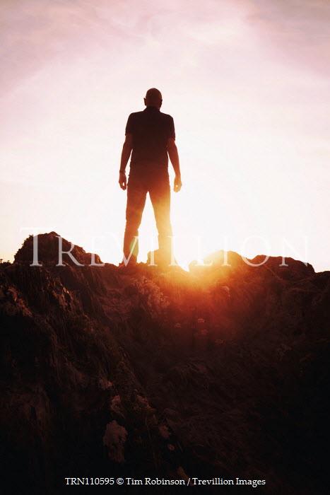 Tim Robinson Man standing on rocks at sunset Men