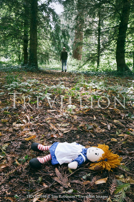 Tim Robinson Discarded doll and distant man in forest Men