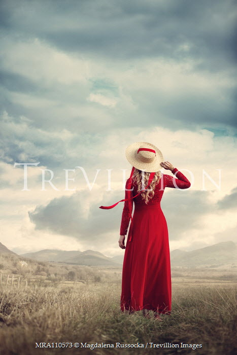 Magdalena Russocka woman in red dress and hat watching mountains