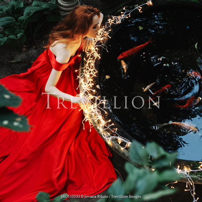 Jovana Rikalo Young woman in red gown sitting by koi pond Women