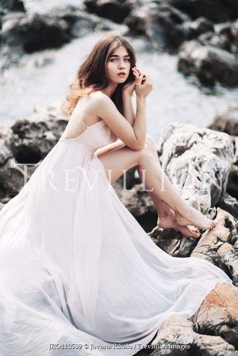 Jovana Rikalo Young woman in white dress sitting on rocks Women