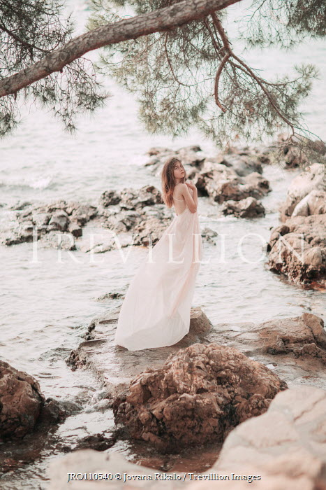 Jovana Rikalo Young woman in white dress standing on rocks Women