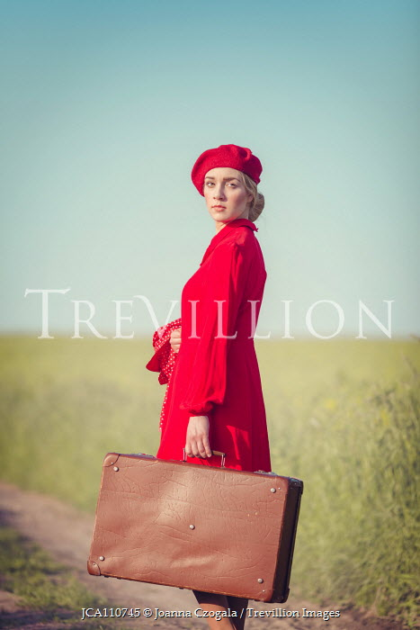 Joanna Czogala RETRO WOMAN IN RED WITH SUITCASE IN COUNTRYSIDE Women