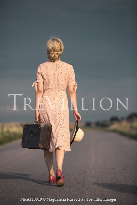 Magdalena Russocka young blonde woman with hat and suitcase walking on country road