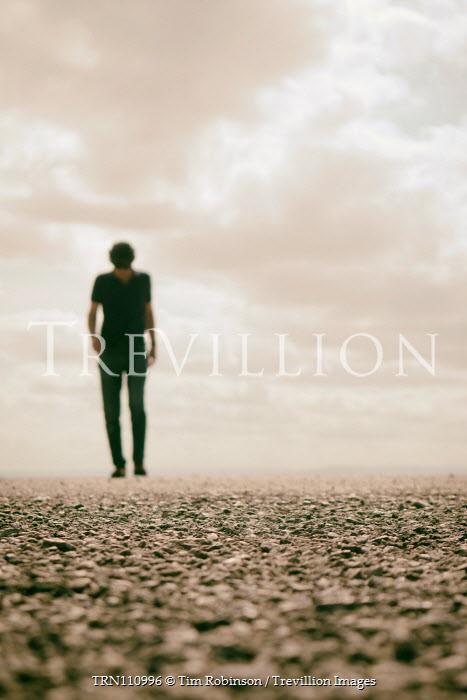 Tim Robinson Blurred man on pebble beach