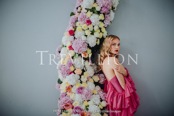 Dasha Pears Young woman in pink dress leaning on flower arch