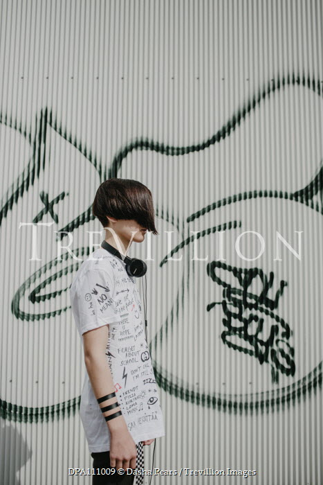Dasha Pears Teenage boy with fringe and headphones by graffiti on wall Children