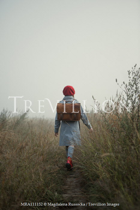 Magdalena Russocka retro girl with school bag walking in misty field