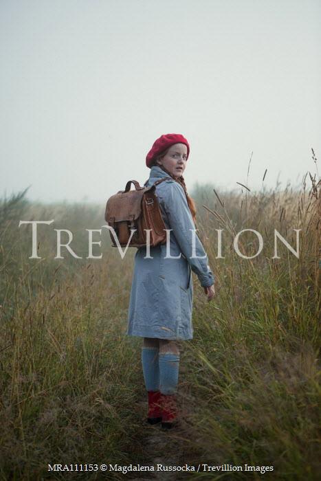 Magdalena Russocka retro teenage girl with school bag walking in misty field