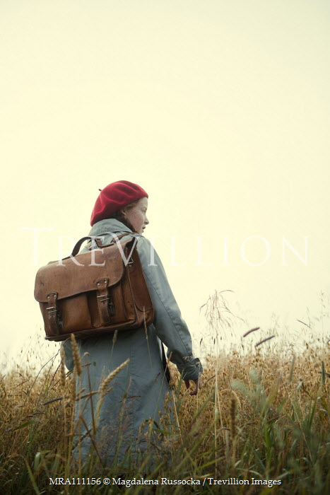 Magdalena Russocka retro teenage girl with school bag standing in misty field