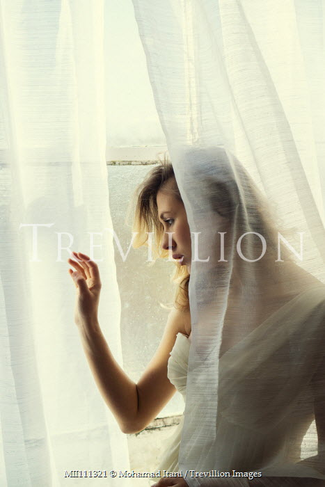 Mohamad Itani Woman in white stares out of window Women