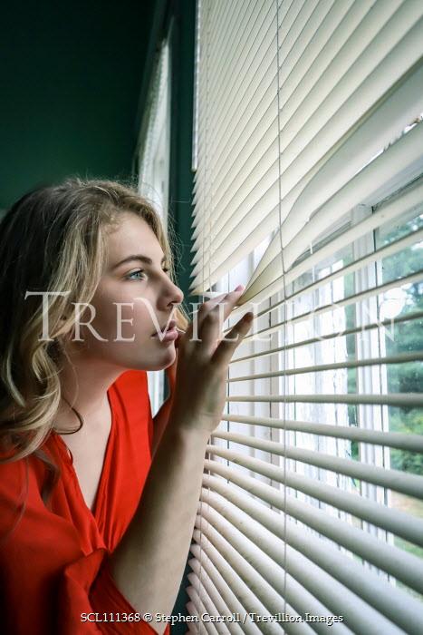 Stephen Carroll Young women peering through blinds Women