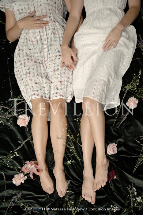 Natasza Fiedotjew Two young women lying in garden cuddling on blanket with flowers from above