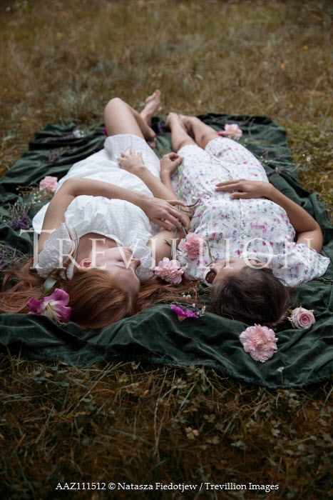 Natasza Fiedotjew Two young women lying in garden cuddling on blanket with flowers