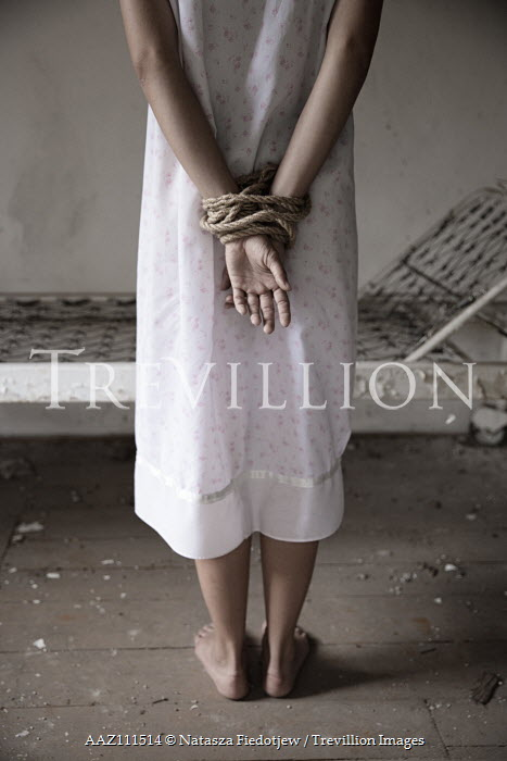 Natasza Fiedotjew Close up of young woman from behind standing indoors with hands tied with rope