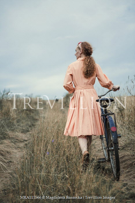 Magdalena Russocka retro woman with bike walking in field