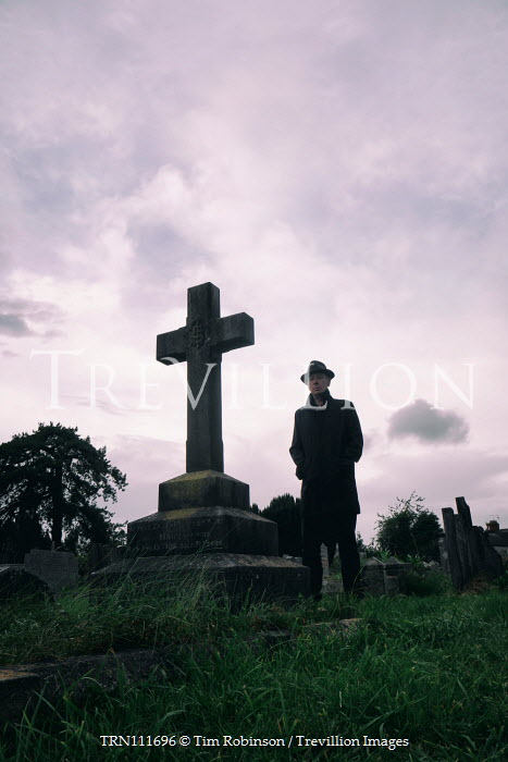 Tim Robinson Man in black coat and hat standing by gravestone Men