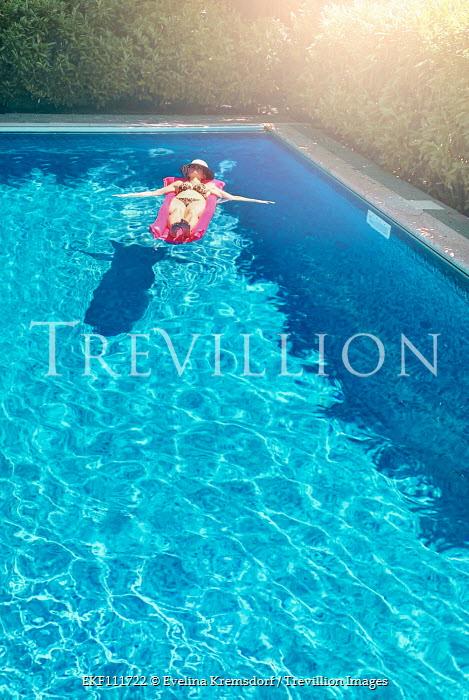 Evelina Kremsdorf Woman in bikini sunbathing on inflatable in swimming pool Women