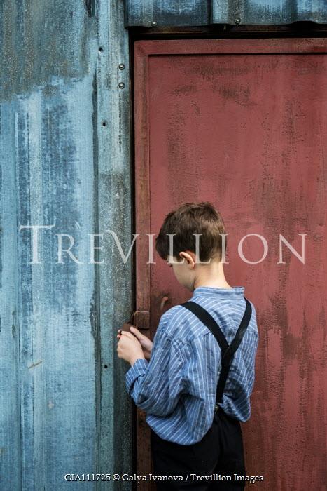 Galya Ivanova Boy opening padlock on door