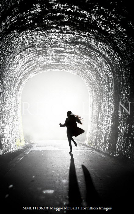 Maggie McCall Silhouette of scared woman running in tunnel