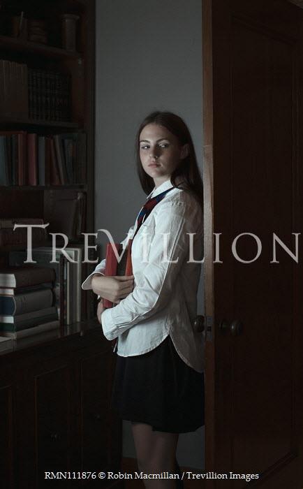 Robin Macmillan Teenage girl holding books while hiding behind library door