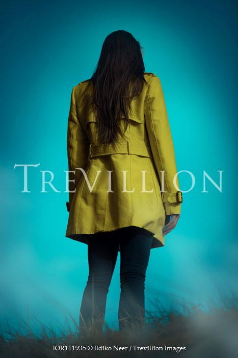 Ildiko Neer Woman in yellow coat standing in grass
