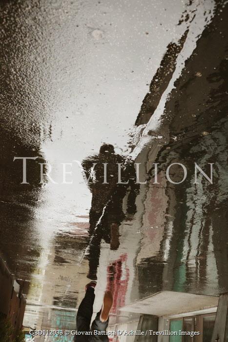 Giovan Battista D'Achille REFLECTION IN PUDDLE OF MAN RUNNING IN STREET Men