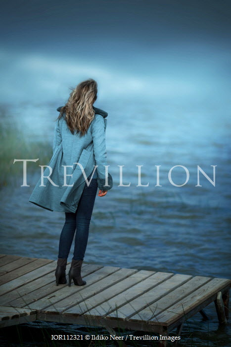 Ildiko Neer Woman in coat standing on jetty