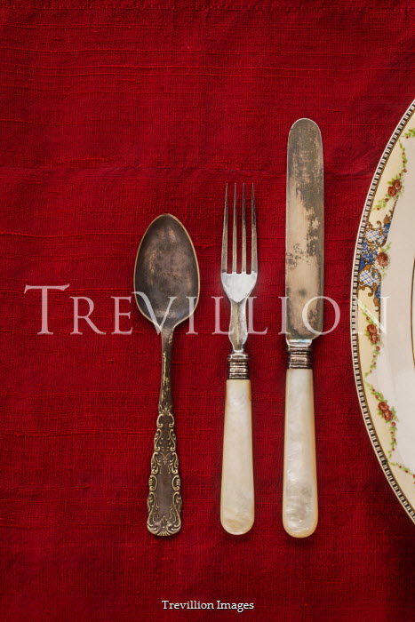 Michael Nelson Antique silverware on red tablecloth