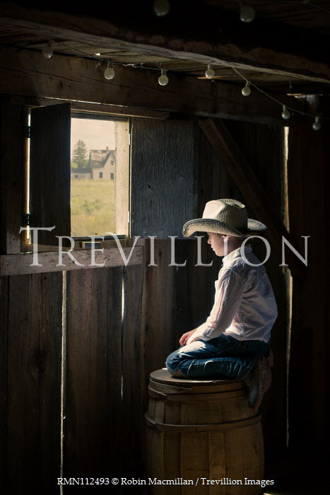 Robin Macmillan Boy with straw hat looking out barn window while sitting on barrel