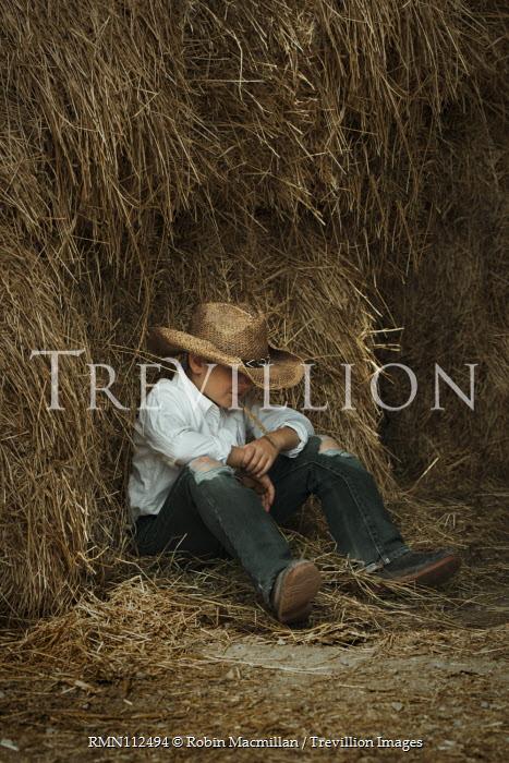 Robin Macmillan Boy with straw hat sitting by hay bales