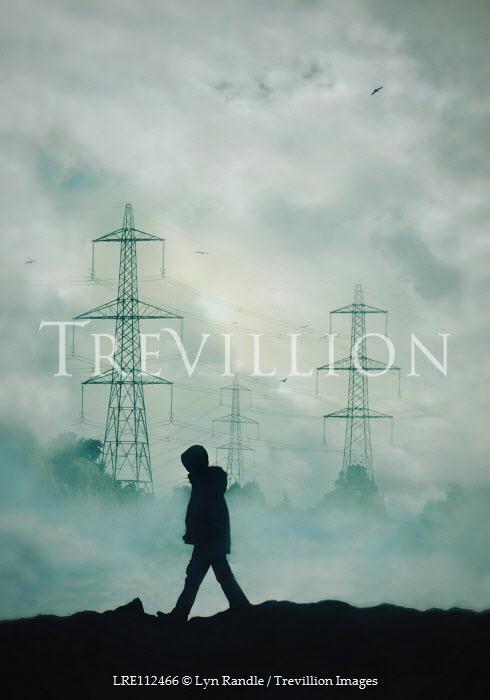 Lyn Randle Silhouette boy in hooded jacket walking by powerlines in fog
