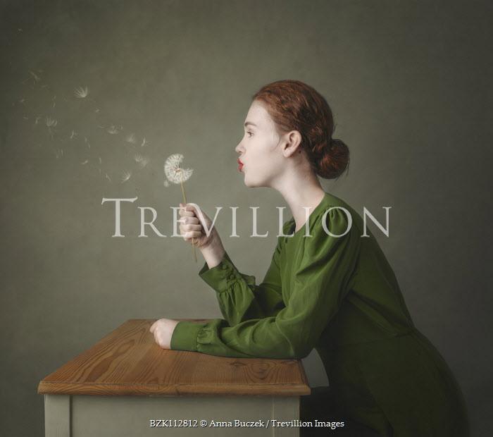Anna Buczek Young woman in green dress blowing dandelion Women