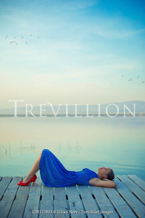 Ildiko Neer Woman in blue dress sitting on jetty