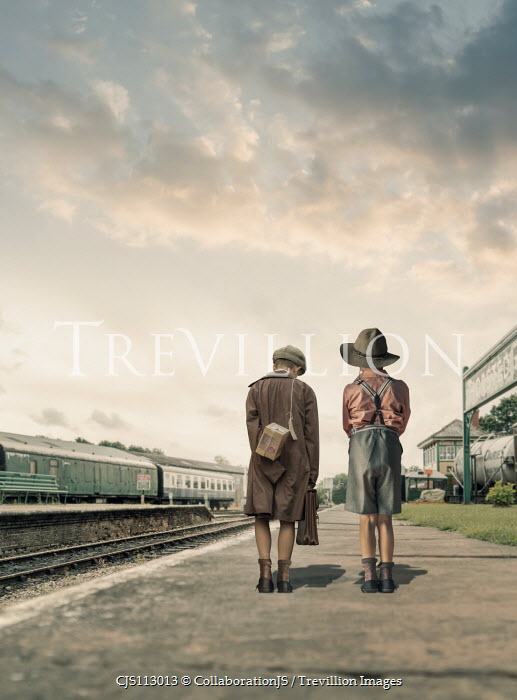CollaborationJS Two  evacuee boys waiting at a train station