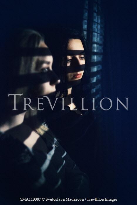 Svetoslava Madarova Women standing in shadow of blinds at night