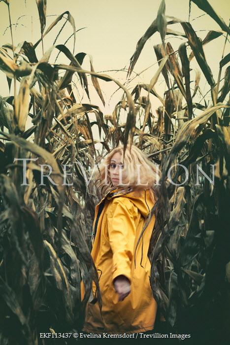 Evelina Kremsdorf Young woman in yellow coat walking in cornfield