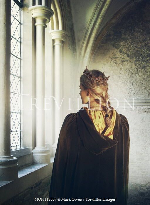 Mark Owen Young woman in Medieval cloak and crown by window