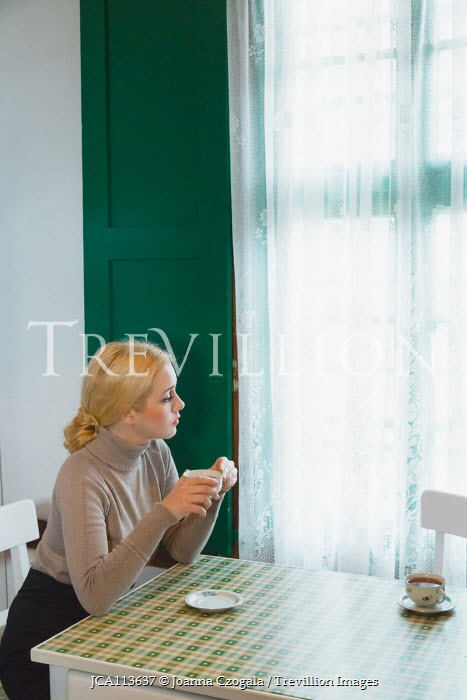 Joanna Czogala Woman with tea cup looking out kitchen window