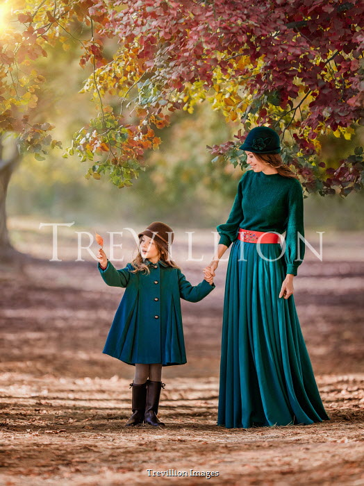 Lilia Alvarado Smiling girl looking at autumn leaf while holding her mother's hand