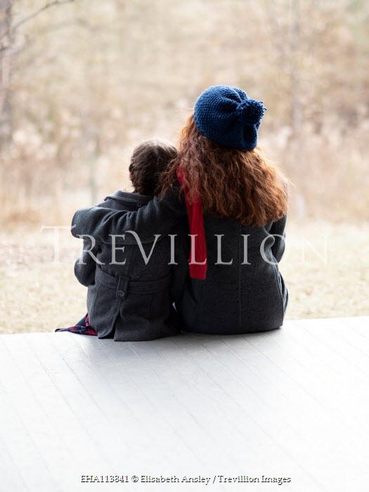 Elisabeth Ansley TWO GIRLS HUGGING ON VERANDA IN WINTER Children