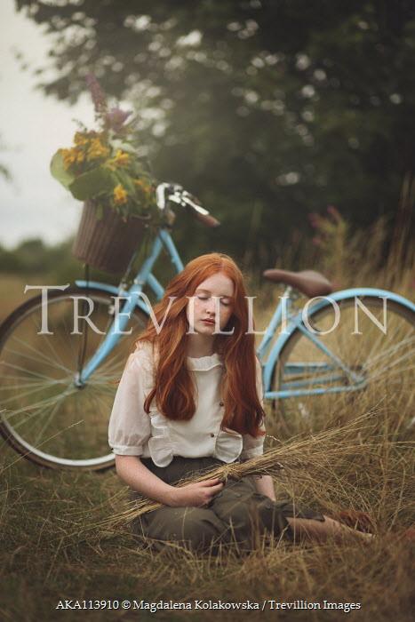 Magdalena Kolakowska Teenage girl sitting in grass by bicycle